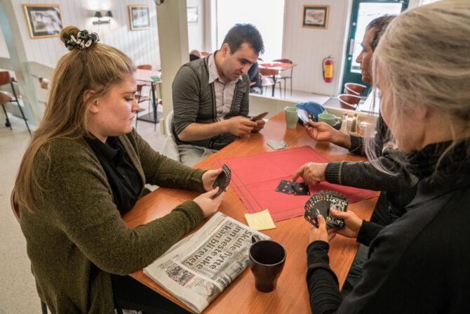 Bildet viser fire stykker som sitter rundt et bord og spiller kortspill.