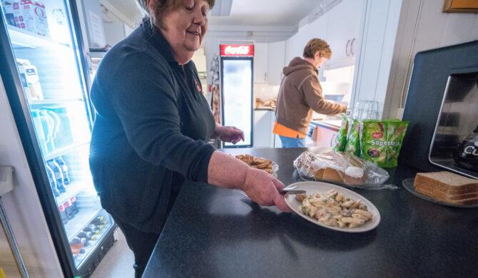 Bildet viser en dame som serverer en pastarett på en cafédisk. I bakgrunnen holder en annen dame på med å ordne noe på kjøkkenet.