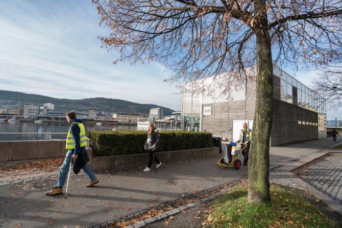 Bilder viser tre stykker som går langs en gangvei langs elva i Drammen. To av de har på gule refleksvester. Den ene triller på en tralle med søppelsekk i. De andre bærer på klyper de plukker søppel med.