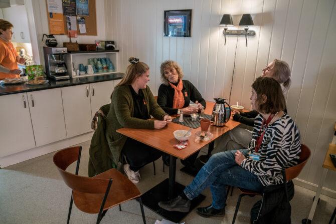 Bildet viser fire mennesker som sitter ved et bord og ler og smiler med kaffekopper og skåler med mat foran seg.