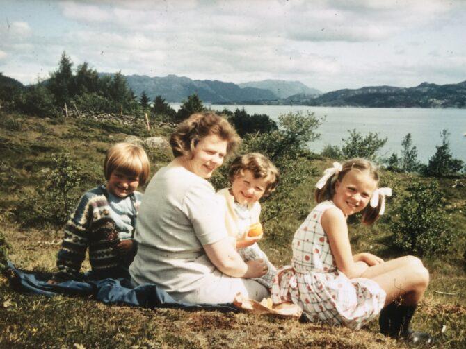 Bildet viser et eldre fargefotografi av en familie som sitter ute i naturen på grønt gress. I bakgrunnen skimtes havet og blå fjelltopper enda lenger bak. Det er moren til Kari Veiteberg som sitter forrerst i bildet, og Veiteberg og to av hennes søstre som barn som sitter sammen med henne.