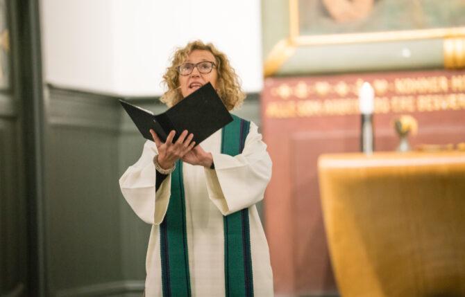 Bildet viser Kari Veiteberg i hvit prestekjole i et kirkerom. Hun holder en svart bok med tekst hun leser fra på hendene sine, med hendene høyt hevet.