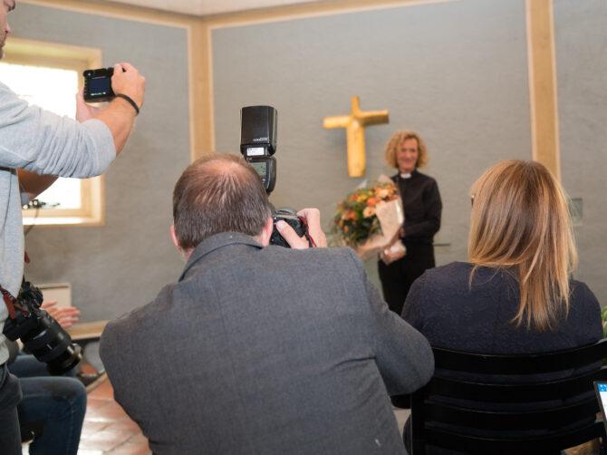 Bildet viser en gjeng med fotografer i forgrunnen med kameraene rettet mot Kari Veiteberg, Oslos nye biskop, som står i bakgrunnen av bildet. På veggen bak henne skimtes et kors av gull.