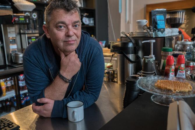 Bildet viser Trond Henriksen som lener seg over en cafédisk mens han ser mot fotografen. Han lener haken under hånda si, og har en kaffekopp foran seg.