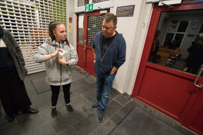 En ung jente står med en flaske og en togbillett i hånda i venterommet på en togstasjon. Ved siden av står en voksen mann som er miljøarbeider på ungdomsklubben hennes og ser ned med hendene i lommene.