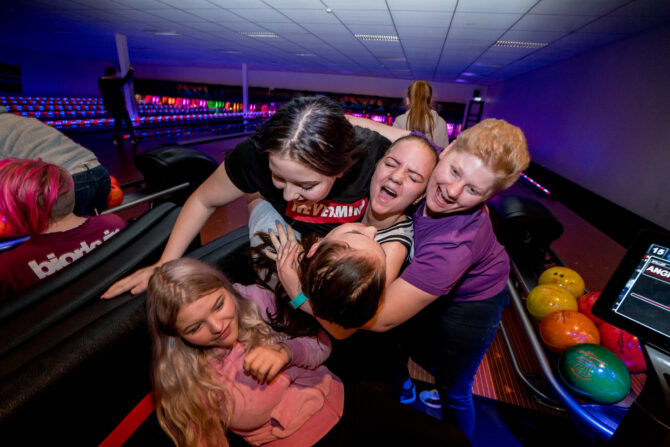 Fire ungdommer finner sammen i en klynge og jubler foran en bowlinghallbane.