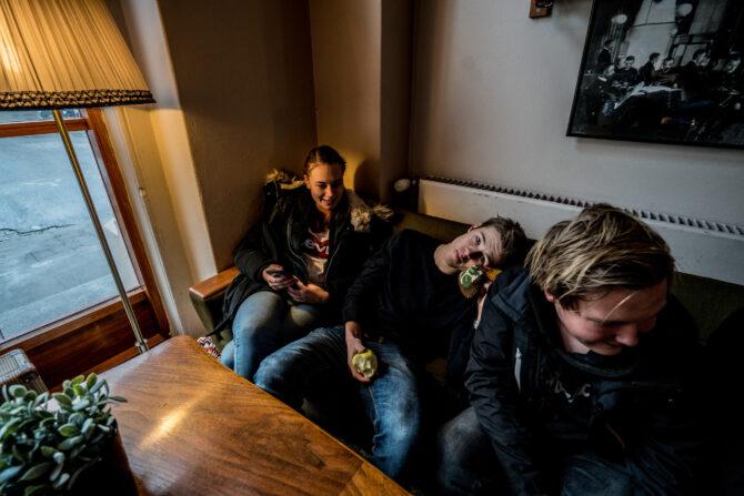 Tre ungdommer sitter i en sofa. Gutten i midten lener seg tilbake og ser opp mot fotografen. Jenta til venstre holder en mobil og smiler mens hun ser mot høyre. Gutten til høyre ser også på noe utenfor bildet.