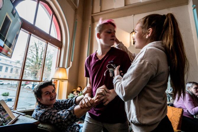 Tre ungdommer holder fast i hverandre og tøyser med hverandre. Gutten til venstre sitter og ser mot kameraet. I midten står en gutt med rosa hår, vendt mot en jente som står til høyre i bildet.