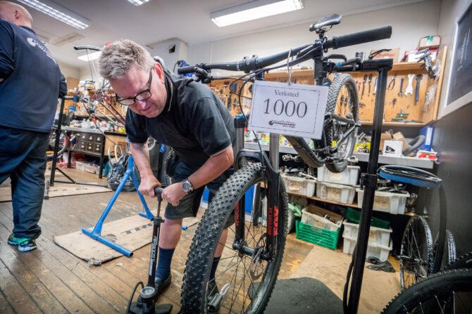 Bilde av en mann som mekker på en sykkel inne på et sykkelverksted.