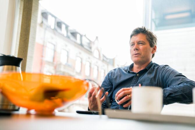 Bilde av en mann i blå skjorte som sitter på andre siden av et bord for fotografen. I forgrunnen av mannen sees en oransje skål og en hvit kaffekopp.