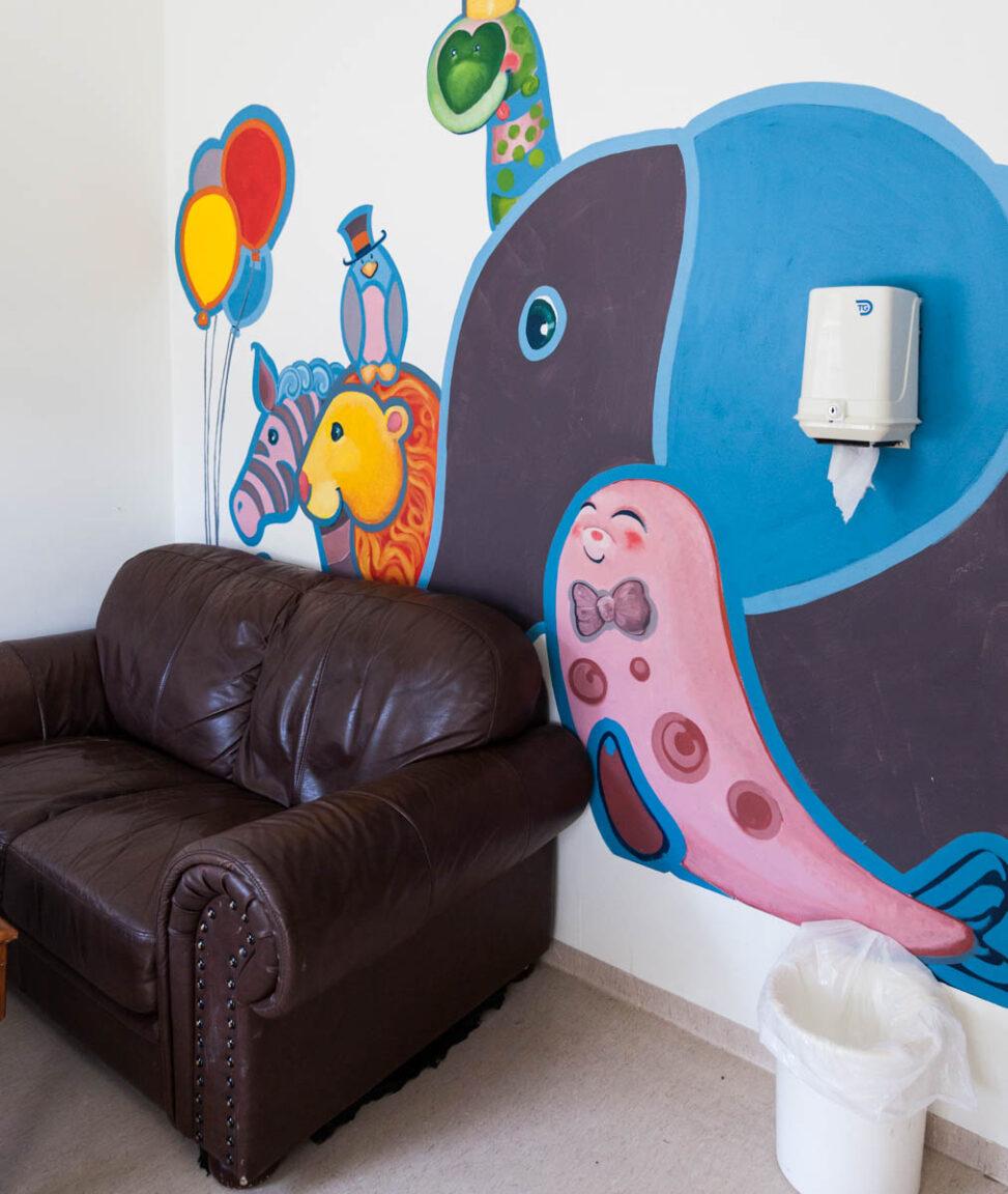 Besøksrommet er pusset opp på dugnad, en av de innsatte har malt de fine tegningene på veggen bak Tone.