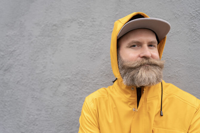 Adam i gul regnjakke som smiler lurt foran en grå sementvegg.