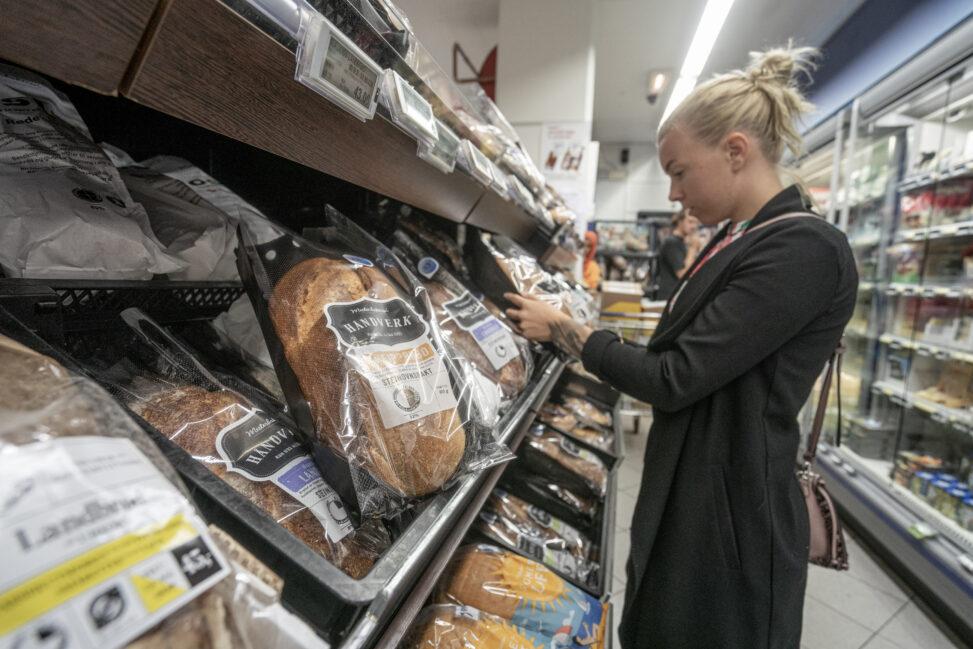 Malin (24) ser på prisen når hun handler mat