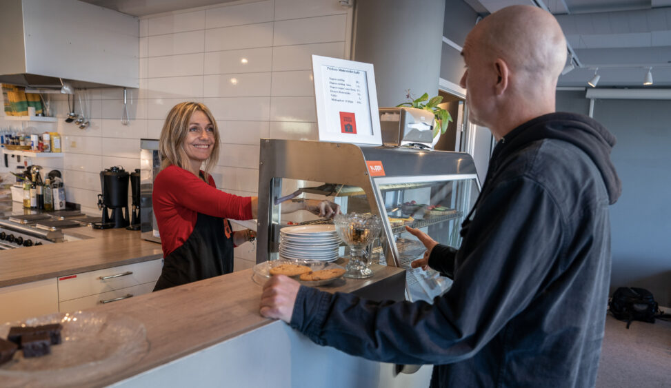 Frivillige og ansatte bak disken på Møtestedet kafé i Bodø møter gjestene.