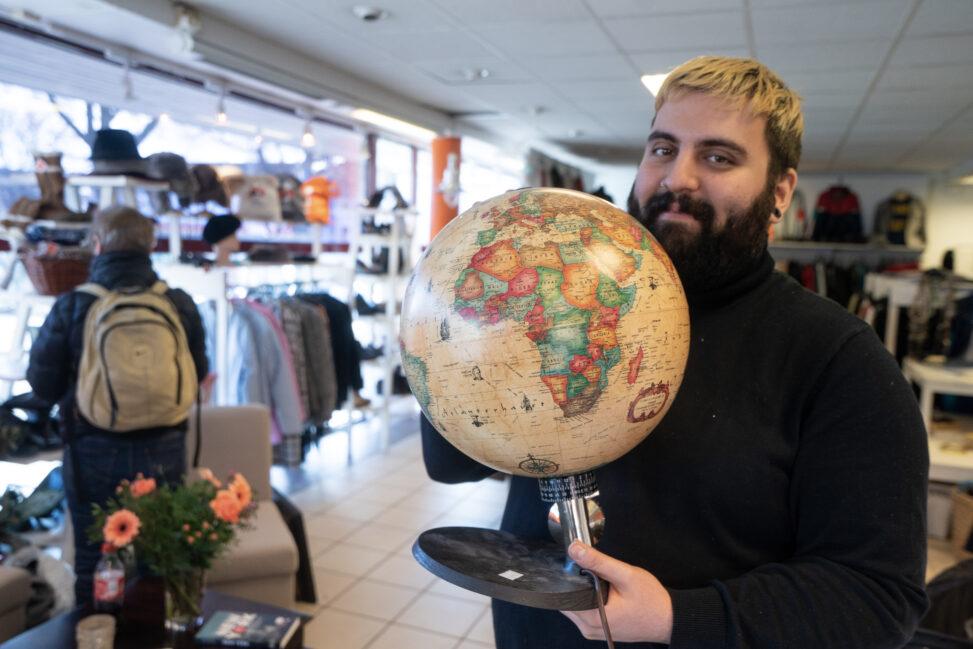 Åmod Lorestani viser fram en globus i Bruktbutikken Drammen