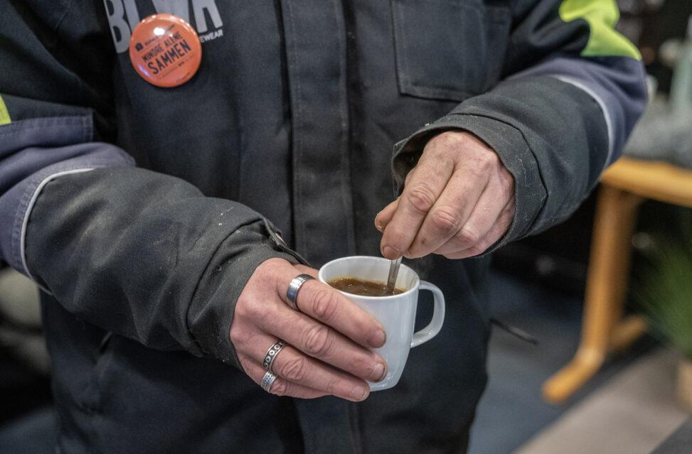 Nærbilde av hender som rører i kaffekopp