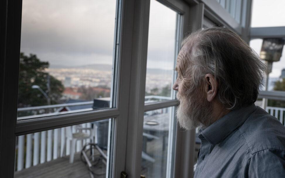 Harald Lunde ser ut av vinduet hjemme på Ekeberg