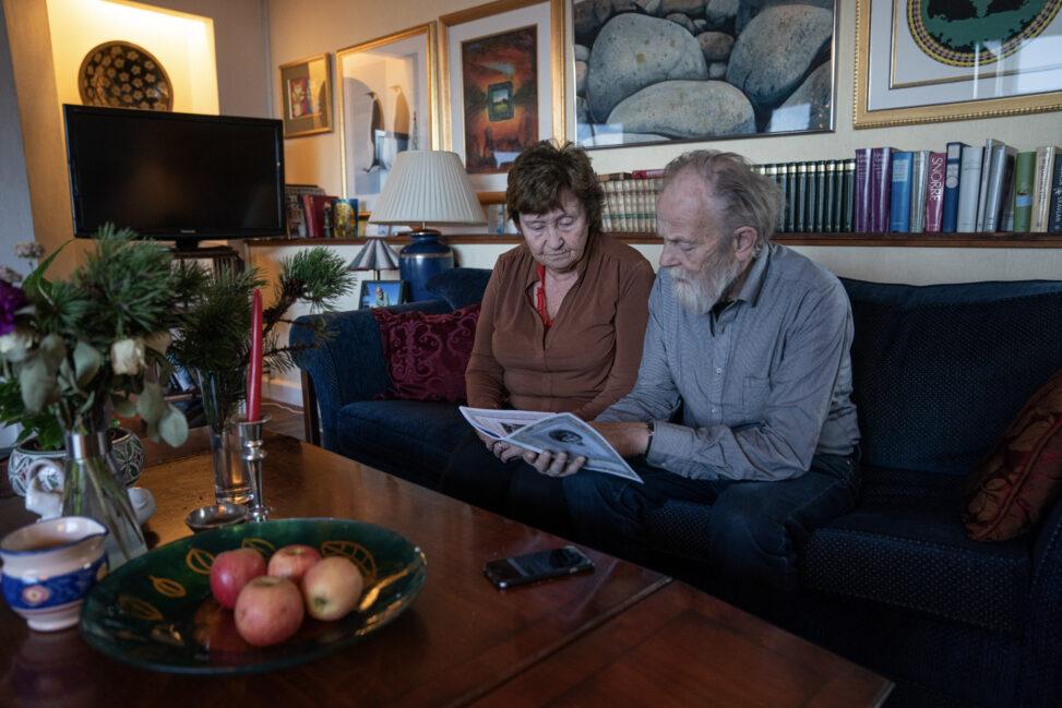 Jorunn og Harald Lunde sitter i sofaen og blar i heftet Jorunns minnebok sammen