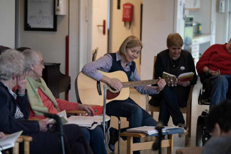 Sykepleier Mette har tatt fram gitaren og satt i gang allsang med deltakerne på dagsenteret