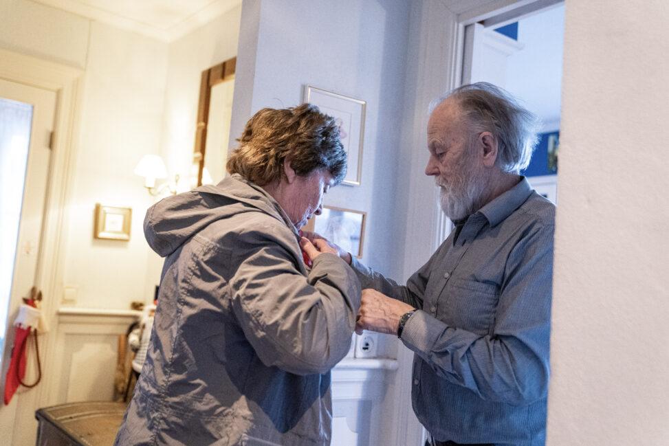 Harald Lunde hjelper kona med å få på seg ytterjakken.