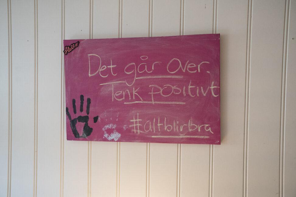 """Bilde på veggen med teksten """"Det går over. Tenk positivt. Hashtagg alt blir bra""""."""